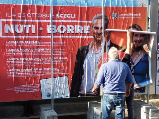 I tecnici della affiggioni al lavoro per sistemare il manifesto di Nuti - Borre